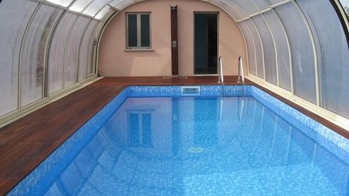Piscina interrata metri 7x3 x h 1,5 riscaldata , con copertura telescopica  Vista interna della piscina coperta con doccia nella parete.