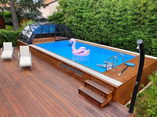 10.Piscina fuori terra con copertura telescopica. Questa piscina fuori terra rivestita in legno di larice ha una pompa di calore per riscaldare l'acqua e la copertura telescopica mobile e impachettabile come in foto